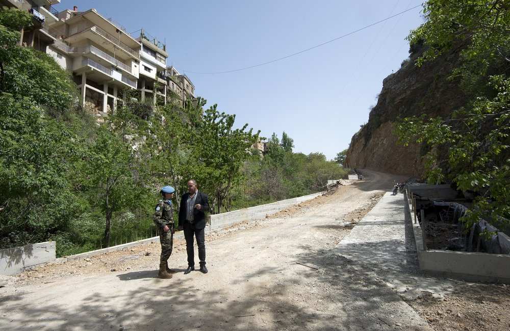 Standing on the completed bridge, a UNIFIL Spanish peacekeeper discusses the construction with Bassem Hashem, Deputy Mayor of Shab'a.
