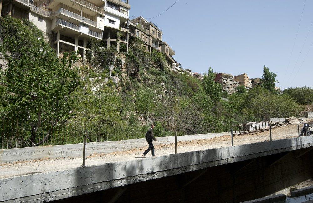 أحد المهندسين المشاركين في أعمال البناء يعبر فوق جسر شبعا الممول من الكتيبة الإسبانية التابعة لليونيفيل.