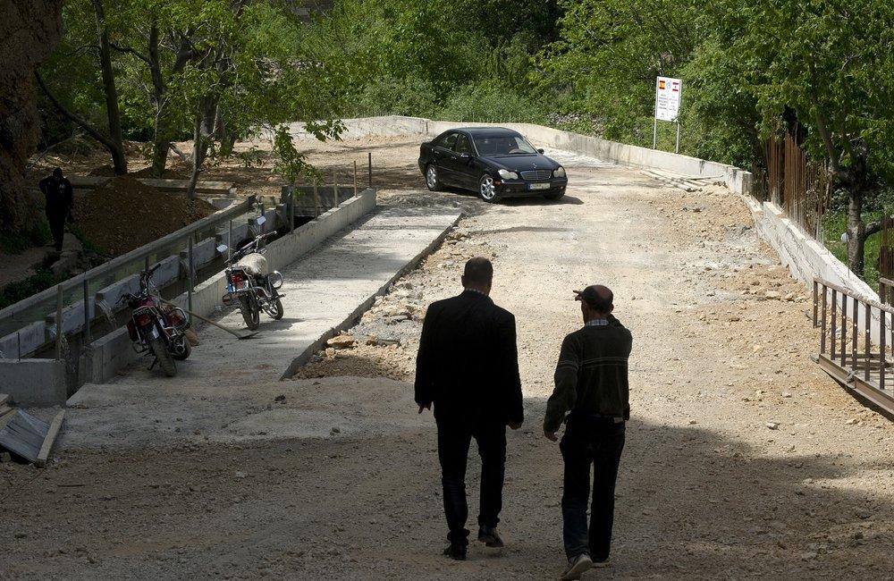نائب رئيس بلدية شبعا وأحد المهندسين يعبران فوق الجسر المنجز.