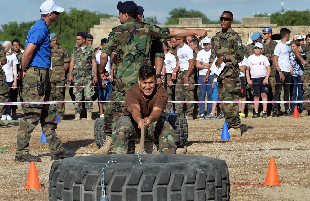 A Lebanese Army soldier pulls a truck tyre.