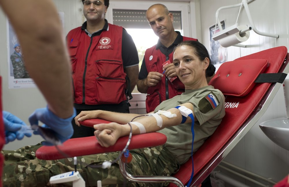 Major Nina Raduha, UNIFIL's Slovenian Contingent commander, donates a unit of blood to the Lebanese Red Cross mobile clinic.