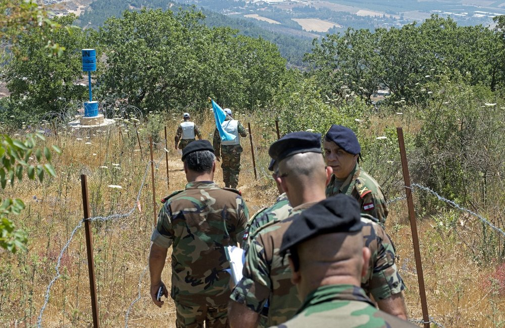 UNIFIL peacekeepers carrying the UN flag lead the LAF geographical team past a blue barrel in Meiss Ej-Jabal, south-eastern Lebanon.