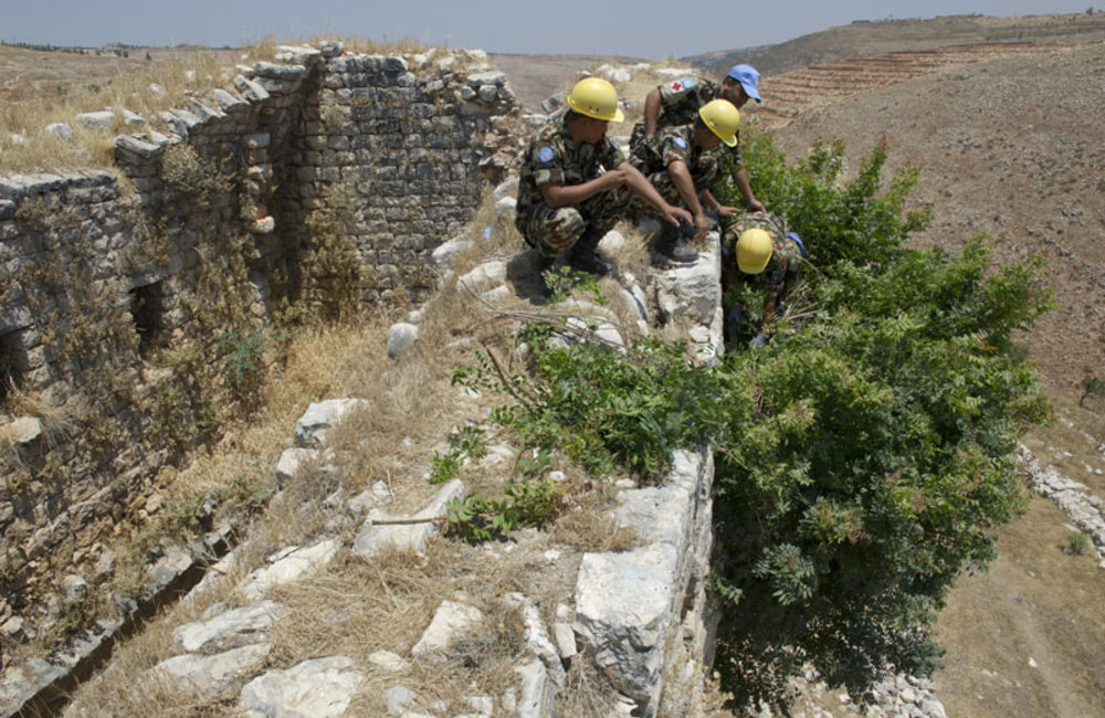 Team of Nepalese peacekeepers cutting vegetation from the castle's walls.