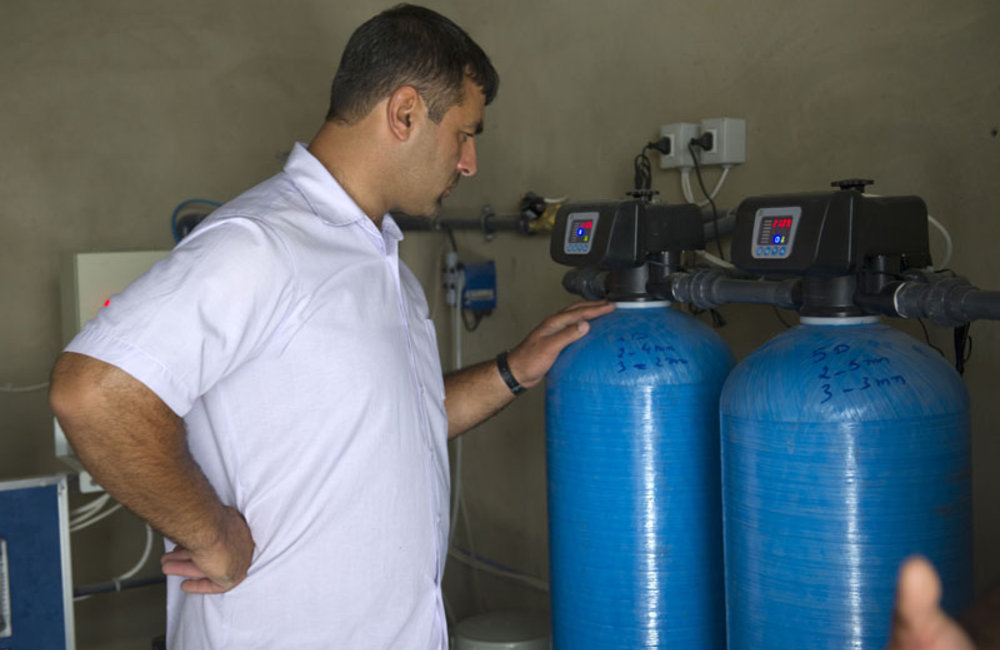 A technician from Tebnin School checking the sand and activated carbo-filter.