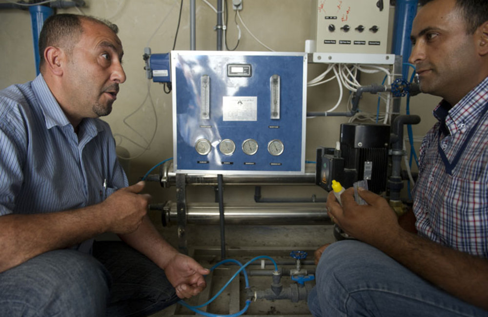 Mr. Zakhia Al Berry explaining about the pressure of reverse osmosis filter to the technician from Arzun.