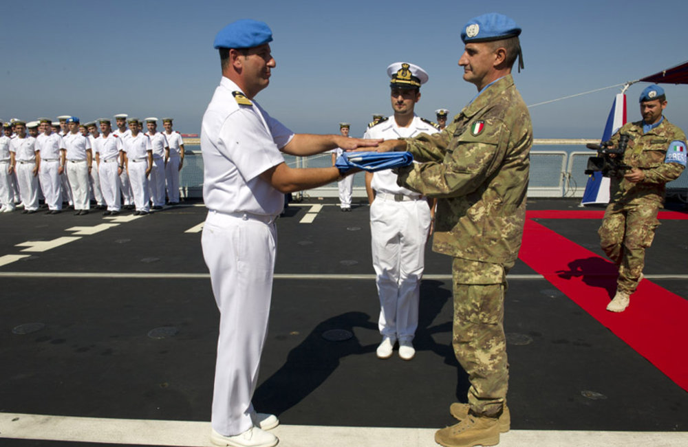 UNIFIL Head of Mission and Force Commander Major-General Paolo Serra hands over the United Nations flag to Captain (Navy) Gianfranco Annunziata on board of the Andrea Doria, the latest ship to join UNIFIL's Maritime Task Force.