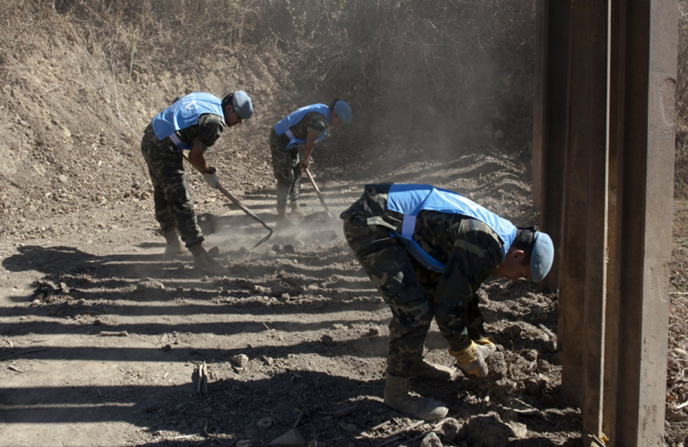 UNIFIL peacekeepers clearing the final segment of the water drainage channel which passes under a fence in the vicinity of the Blue Line.