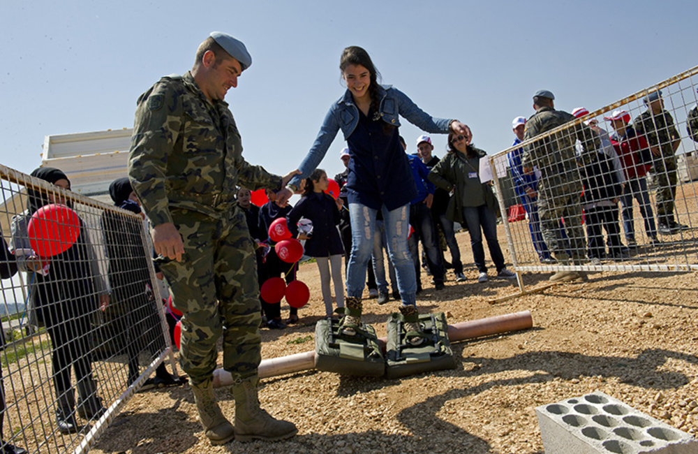A Lebanese student with a UNIFIL peacekeeper at UN Position 7-2 in Sector East trying for herself demining inflatable shoes during the International Day of Mine Awareness.