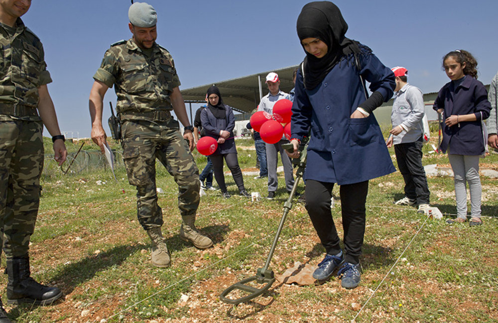 School student practicing with a metal detector in a mock mine field at UN Position 7-2 in Sector East during International Day of Mine Awareness.