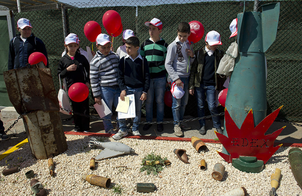 School students standing in front of explosive shells recovered after the war during a briefing about unexploded devices and its dangers at UNIFIL Sector East HQ.