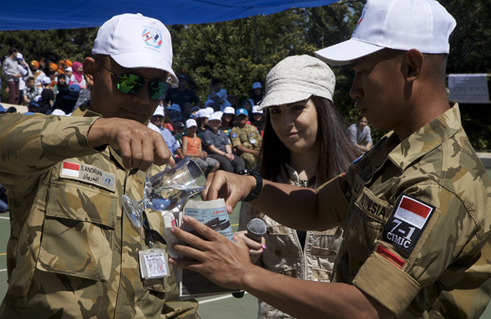 Two Indonesian peacekeepers performing magical tricks.