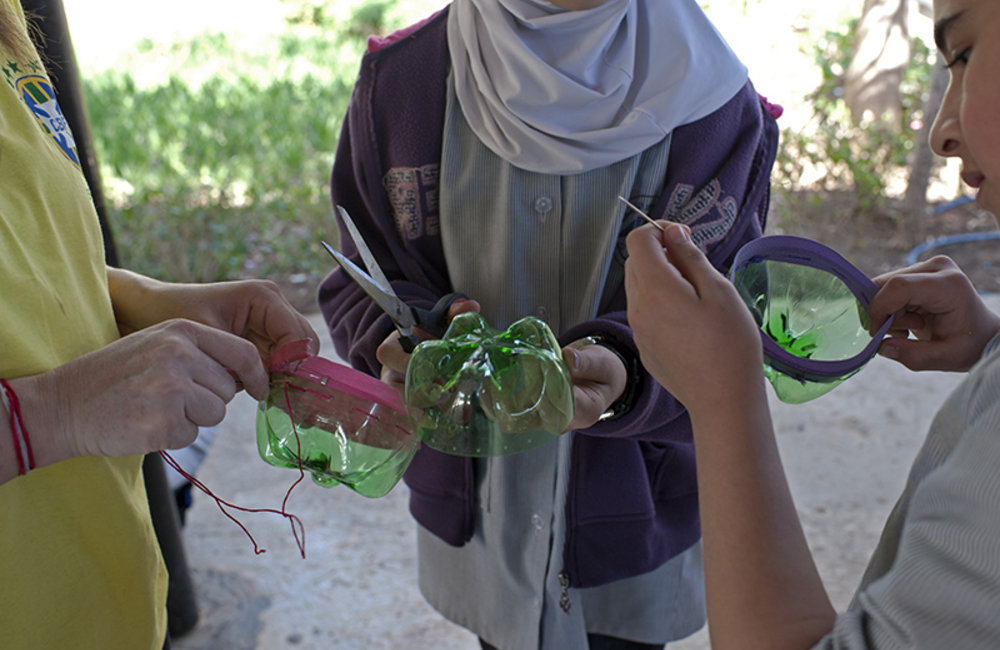 Two girls from Tyre public schools learning how to make art craft with plastic trash.