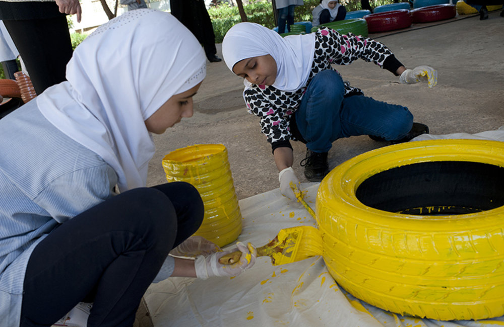 Two girls painting a recycled tire a Tyre public school.