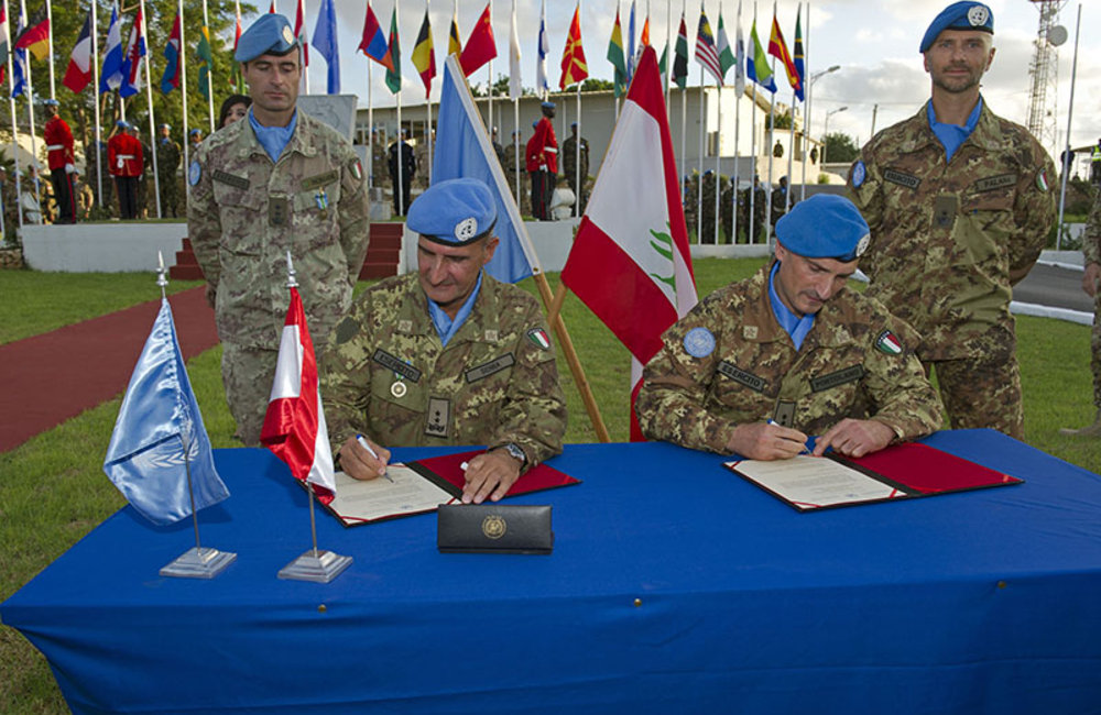 Major-General Serra (left) and Major-General Portolano (right) sign the transfer of command.