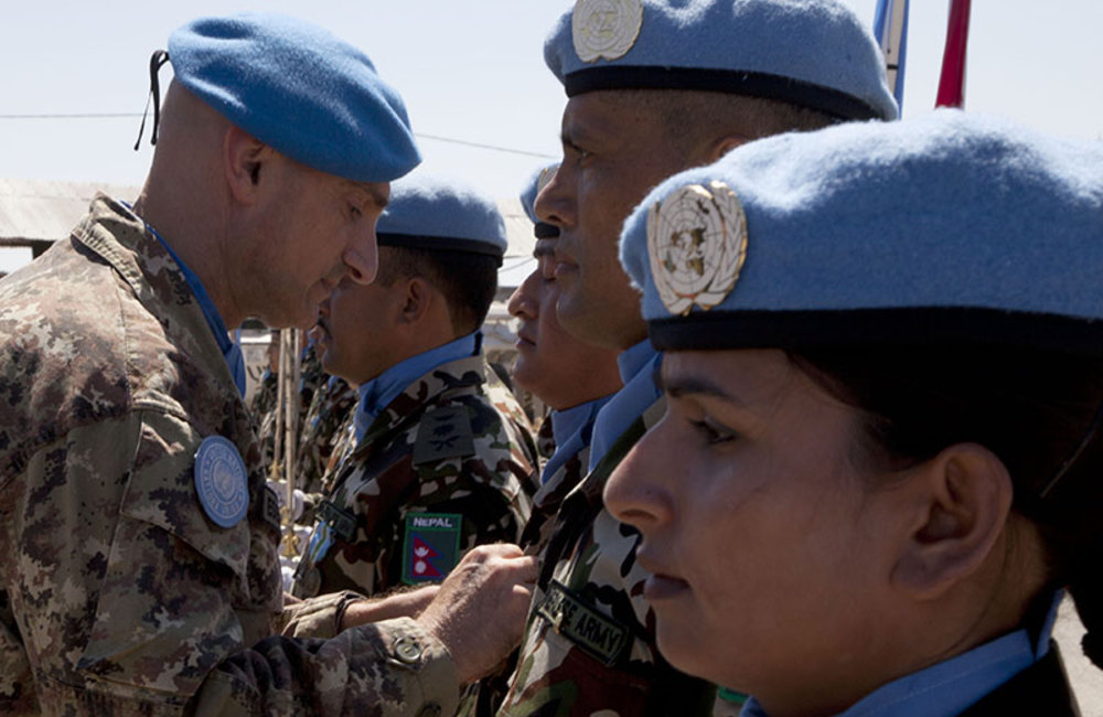 Major-General Luciano Portolano, UNIFIL Force Commander and Head of Mission awards United Nations peace medal to Nepalese peacekeeper.