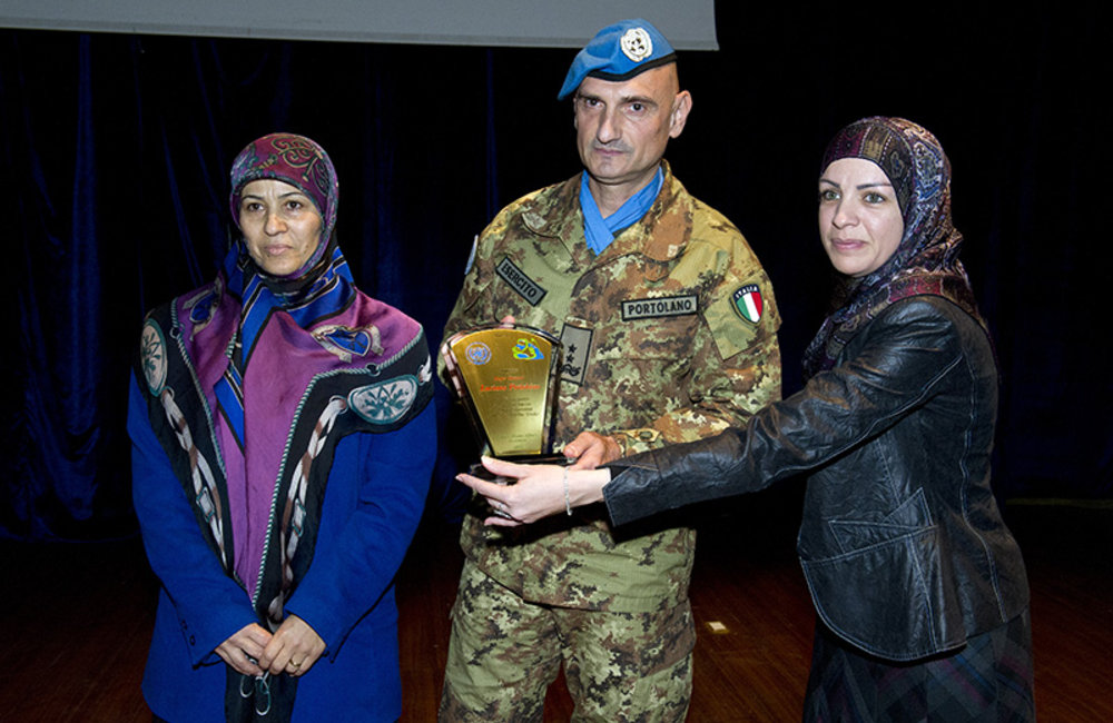 Head of Mission and Force Commander Maj.-Gen. Luciano Portolano receives a plaque from representatives of the women's working groups who spoke about women's perspective on peace.
