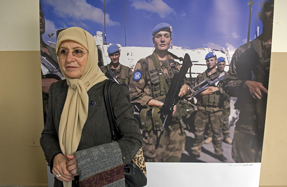 Attendees at the Open Day on Women, Peace & Security stands beside the photography exhibition on women in peacekeeping.