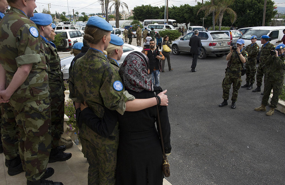 UNIFIL peacekeepers take a group photograph outside the Bassel Assad Cultural Movement Centre with a speaker from the women's working group.