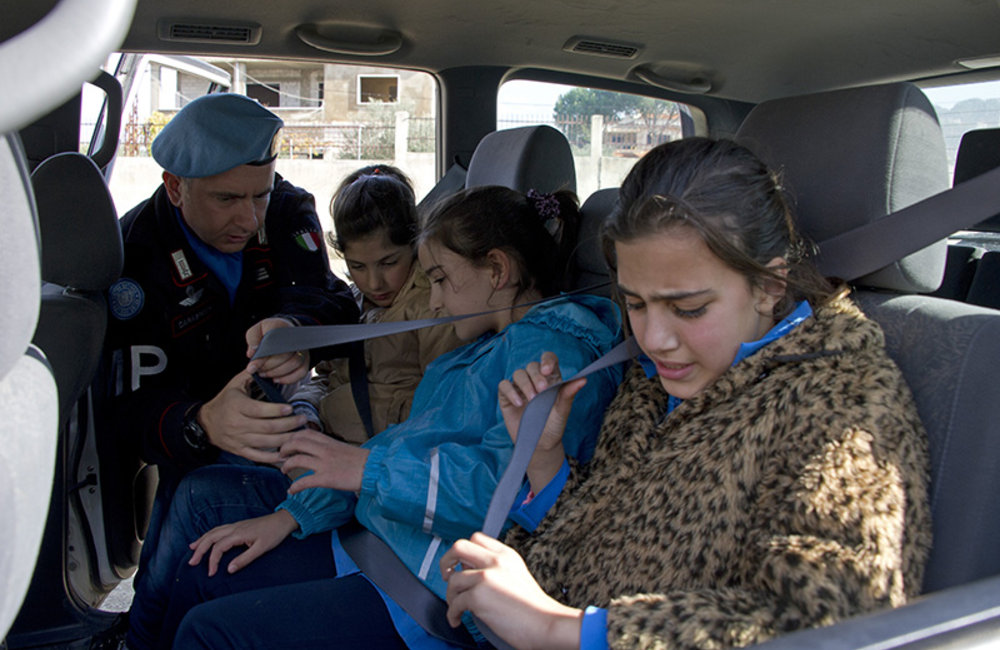 Children learn to wear seatbelts while in a vehicle, with help from an Italian Carabiniere (Military Police) during the road safety awareness campaign conducted in south Lebanon schools.
