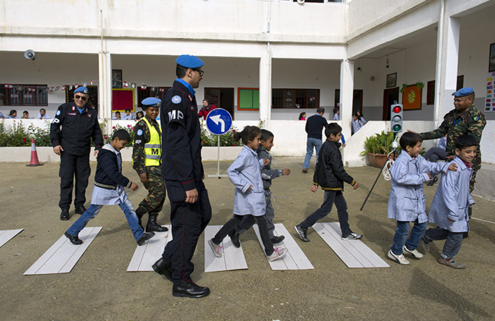 Italian Carabiniere (Military Police) and Tanzanian peacekeeper teach children the use of pedestrian crossing and traffic signals at the road safety awareness campaign.