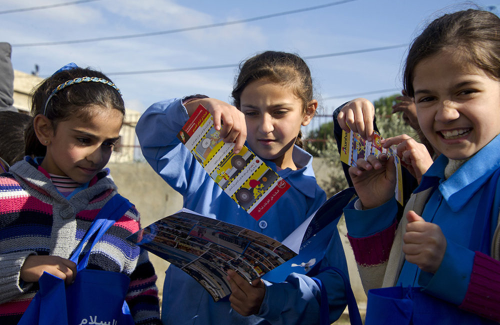 Children receive a goodie-bag with leaflets explaining safe behavior on roads and other useful information at the road safety awareness campaign.