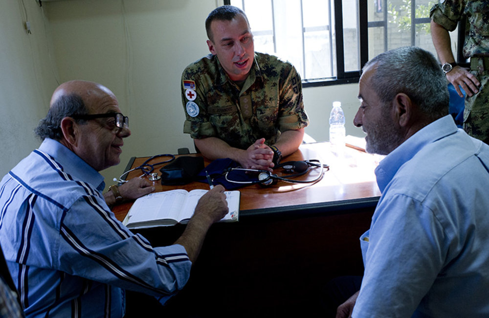Serbian Doctor Major Jovanovic Stevan talks to a villager in Deir Mimas, south Lebanon with help from a translator.