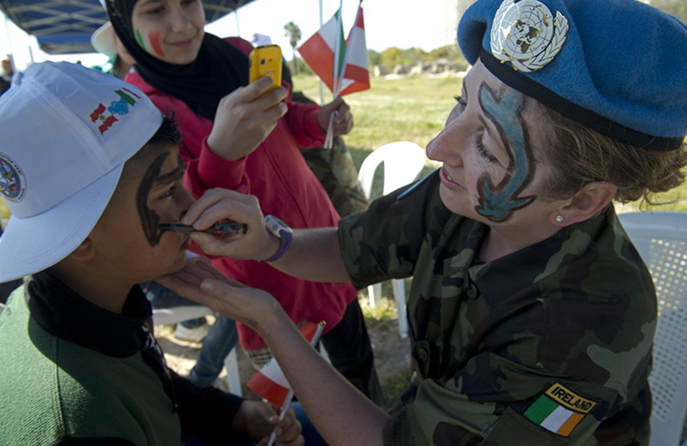 Irish soldier painting the face of a participant.