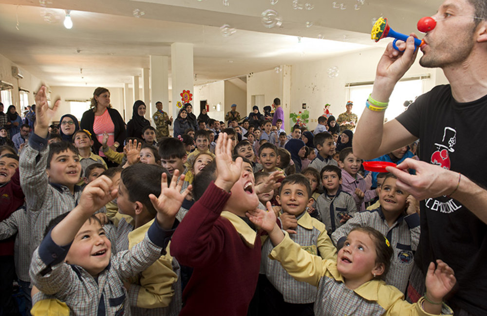 Italian clown blowing soap bubbles to children at Ayta Shaab Care Centre for Children with Special Needs during clown therapy event organized by UNIFIL.