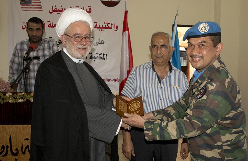 Lt.Col Zunaidi Hassan, the deputy commander of the Malaysian Battalion, presents a plaque of appreciation to Sheikh Hussein Darwish,the Imam of Barish.