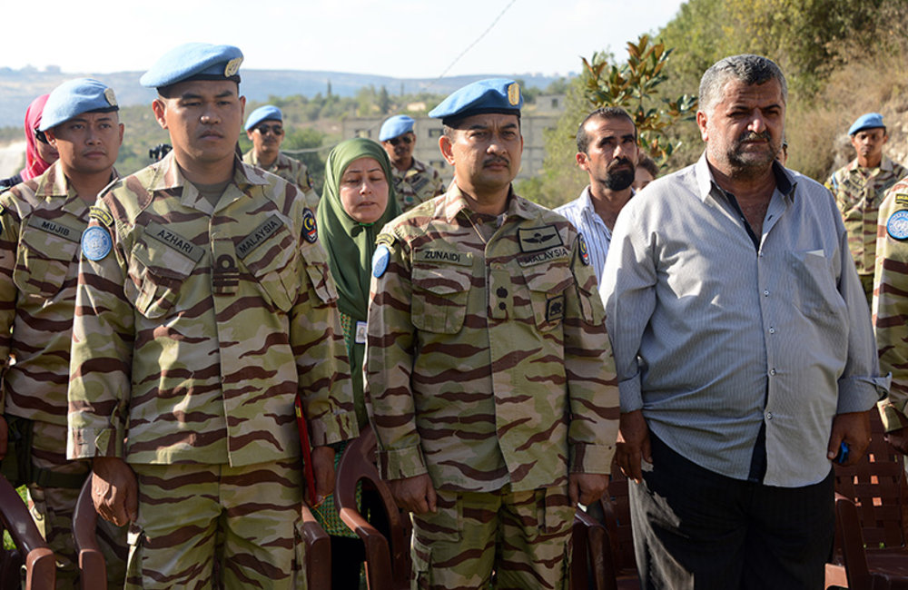 Lt.Col Zunaidi Hassan, the deputy commander of the Malaysian Battalion, and Mr. Taan Harb, the mayor of Hallusiyat, stand in respect for the Lebanese and UN anthems.