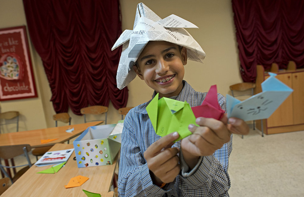 Finished! A delighted child from Al Imam Sader Foundation in Tyre holds up his finished origami.