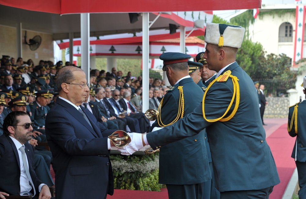 Michel Aoun, President of Lebanon, hands a sword to a newly graduated LAF cadet at the Army Day event.