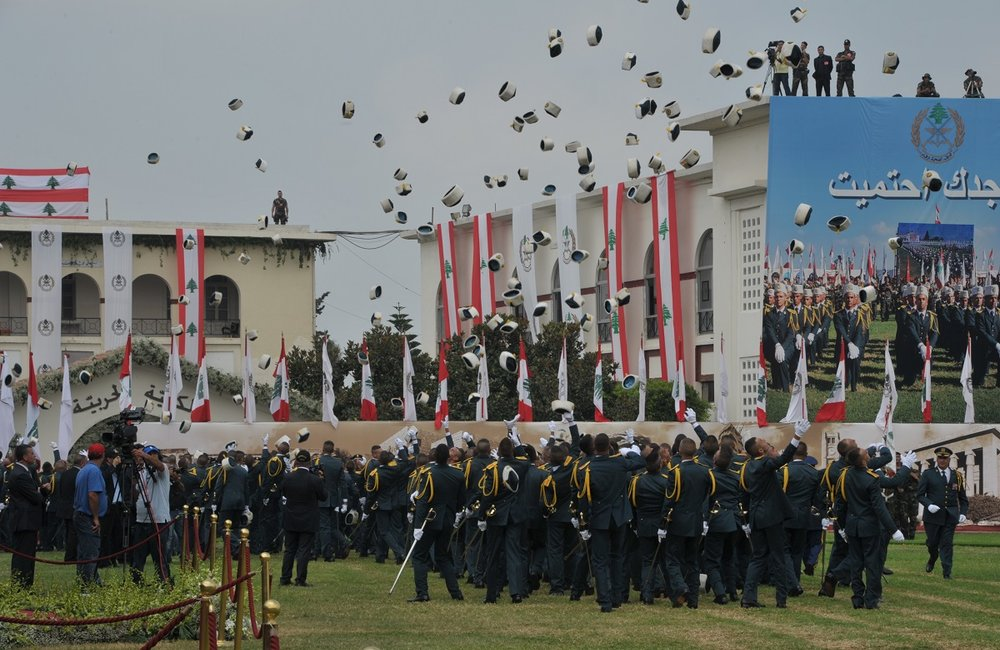 Cadets throwing their hats in celebration at their graduation at the Lebanese Army day event.