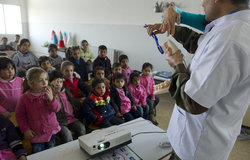 Major Atul Gupta shows students at El Hebbariye Public School how to brush their teeth.