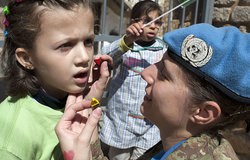 UNIFIL Peacekeeper painting on a girl's face at World Water Day celebration held in Tyre, southern Lebanon.