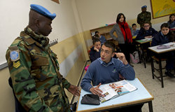 Sergeant Martin Esang from UNIFIL's Ghanaian Battalion working with one of his English class students.